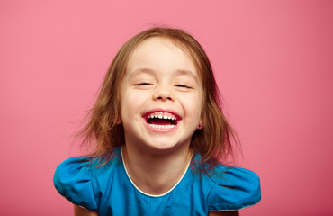 Frontal shot of laughter joyful little girl stands beside pink wall.