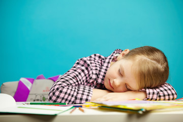 Isolated portrait of sweet sleeping girl at desk during class or hometask. Tired child fell asleep in school.