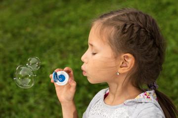Portrait of funny lovely little girl blowing soap bubbles