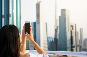 Girl taking picture of Dubai cityscape