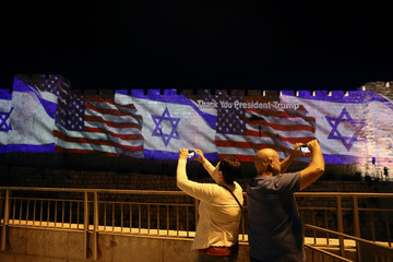 People take pictures of the U.S. and Israeli national flags as projected on a part of the walls surrounding Jerusalem's Old City