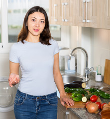 Portrait of young girl housewife standing at home kitchen
