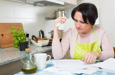 Frustrated woman with banking documents indoors