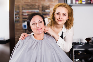 Woman is satisfied with work of adult haircutter