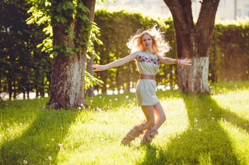 tender woman blonde walks on the grass against the backdrop of the evening sun, dressed in a natural ethnic dress, stylish and cozy. The concept of nature's love