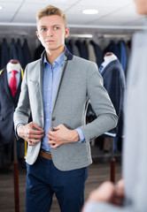 man costumer trying jacket in mirror indoors