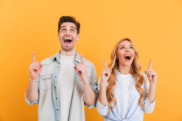 Image of excited man and woman in casual clothing smiling and looking upwards with pointing finger at copyspace, isolated over yellow background
