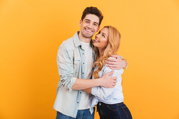 Portrait of young lovely people man and woman in basic clothing hugging together with happy smile, isolated over yellow background