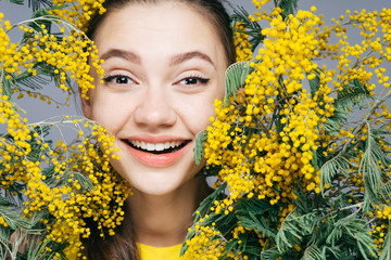 a cute young girl rejoices in the spring and laughs, holds a fragrant yellow mimosa