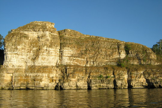 Beautiful rocky shore of the lake in summer in the afternoon - the mountain above the water against the blue clear sky