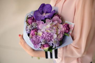 Girl holding a beautiful bouquet of tender violet flowers