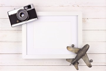 Travel concept mock up with frame, airplane decor and camera on rustic white wood background. Flat lay with copy space.