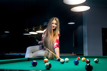Woman sitting on billiard table and going hit ball