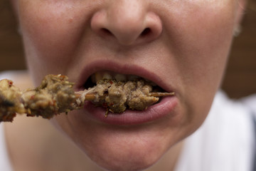 Eating Meat. Closeup Of Woman Mouth Biting Tasty Beef or lamb kebab. Close-up Of Beautiful Female Mouth Eating Delicious Grilled Meat. Nutrition Concept.