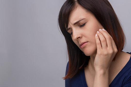 Closeup portrait of young woman on grey background suffering from toothache, holding fingers to jaw and closing eyes from pain.