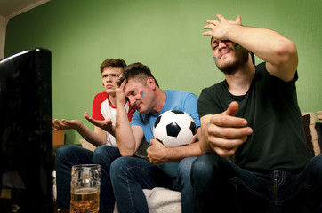 Family watching their team loss on television , sad face expression