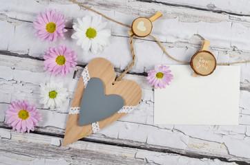 Fototapeta Pusta kartka na życzenia na tablicy drewnianej oraz serce i kwiaty obraz