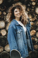 Amazing happy curly woman with a skateboard in her hand posing at the photographer laughing against a wood wall.