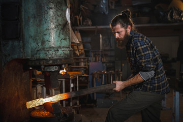 Brutal blacksmith works in his workshop on a mechanical hammer holding a metal part in his hands. Portrait of a profession.