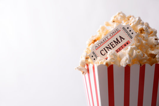 Popcorn and movie tickets on white background top view