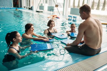 Trainer works with aqua aerobics group, swimming