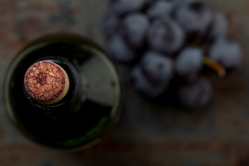 Top view of red wine bottle. Macro selective focus on wine cork. Wine bottle, wine glass and grape on vintage background. Copi space, wine concept