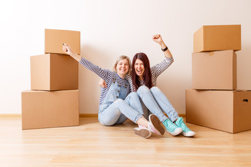 Photo of young blonde and brunette on floor among cardboard boxes