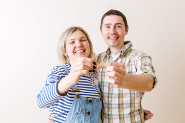 Image of woman and man with keys from apartment against blank wall