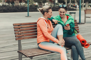 Happy two girls are talking and laughing while sitting on bench outdoor. Lady is showing smartphone to her friend. They are wearing sportswear