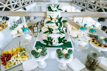 White wedding cake decorated with cream and fruits