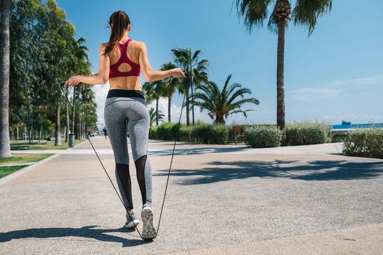 Sporty young woman is jumping on skipping rope on the seafront. Focus on back. Copy space