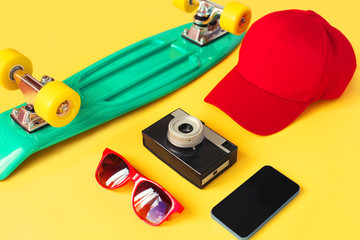 Fashion look concept. Skateboard, red sunglasses, camera, screen smartphone, baseball cap on a yellow background, top view