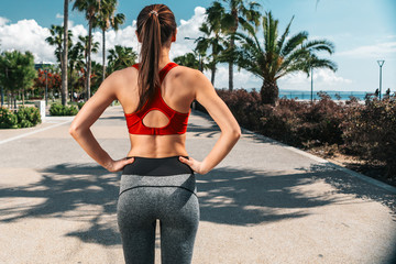 Focus on sporty girl back. She is standing on seafront road and ready for running. Summer activity in tropical place concept