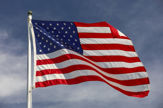 American flag waving in the wind with blue sky and white clouds in the background.