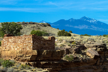 The Box Canyon ruin inside Wupatki National Monument in northern Arizona protects an ancient Native American pueblo site. This image shows the San Francisco Peaks in the background