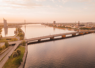 Beautiful aerial view of the Riga old town by the river Daugava and bridges over it. Panoramic Riga scene during sunset.