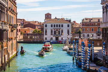 Venice, Italy. Beautiful Venice narrow canals, with many classic gondolas, amazing old rusty buildings, near old cathedral of Santa Maria della Salute.