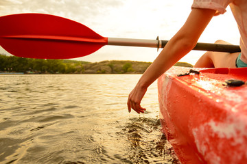 Young Woman Playing with Water while Sitting in Kayak on Beautiful River or Lake at Sunset. Close up of Female Hand.
