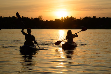 Young Couple Paddling Kayaks on the Beautiful River or Lake under Dramatic Evening Sky at Sunset