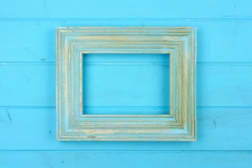 Empty rustic blue wooden frame against a blue wood background. Copy space.