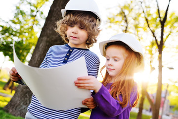 two children - boy and girl in construction helmets looking at white sheet of paper or drawing and smiling