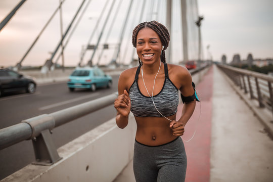 Fit african american woman running while listening to music through earphones