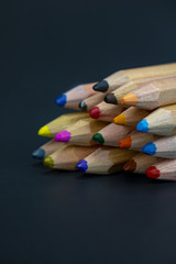 A set of brightly colored wooden pencils sits on an isolated black background with room for text and more items!