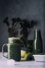 Green smoothie in jar with apple,baby spinach, parsley and banana, over a green round plate on a gray board against a gray background with parlsey leaves.