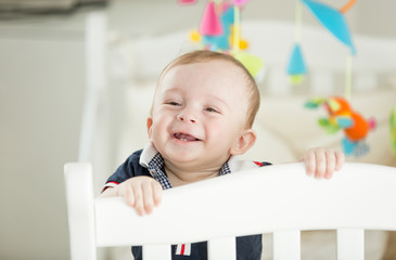 Portrait of happy smiling baby boy with 2 teeth standing in crib