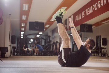 one young man, ordinary average man, exercise abs, arms extended high in air, sitting on floor, in gym. Unrecognizable people behind (out of focus).
