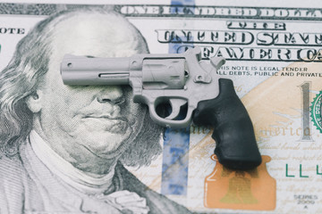 American subcultures that glorify guns and value them more than people metaphor, gun control policy in US, miniature toy guns on Franklin blind eyes and face of US dollar banknote