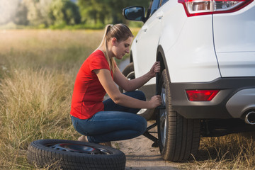 Toned image of young woman changing car flat tire with spare field in field