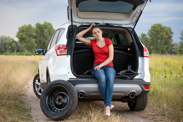 Upset young woman sitting in open car trunk and waiting for help to change flat tire