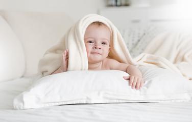 Portrait of adorable 9 months old baby boy lying on bed under big soft blanket